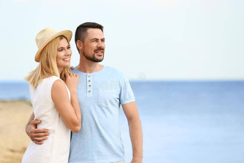 Happy romantic couple  time together on beach, space for text stock images