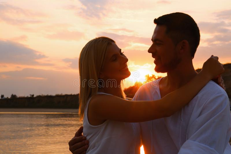 Happy romantic couple  time together on beach at sunset. Happy romantic couple spending time together on beach at sunset stock photo