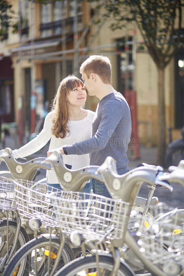 Happy romantic couple of tourists taking bikes for rent in Paris royalty free stock photos
