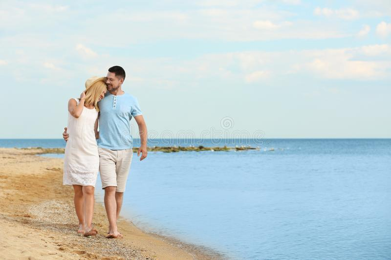 Happy romantic couple walking on beach. Space for text stock photography