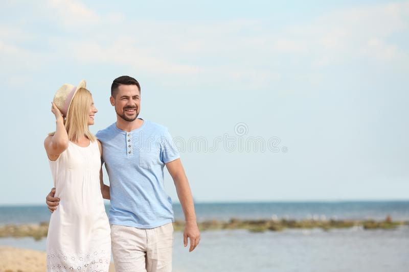 Happy romantic couple walking on beach,  for text. Happy romantic couple walking on beach, space for text royalty free stock images
