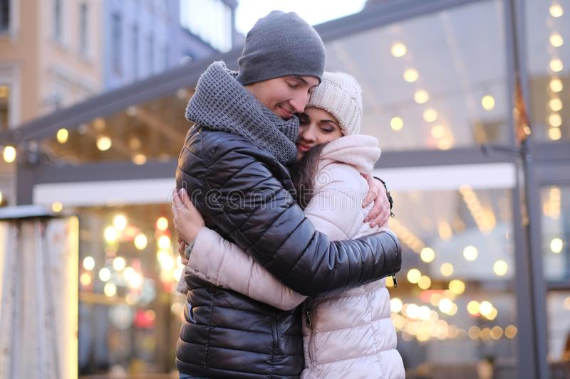 A young romantic couple wearing warm clothes hugging together in evening street near a cafe outside at Christmas time. Happy romantic couple wearing warm clothes royalty free stock images