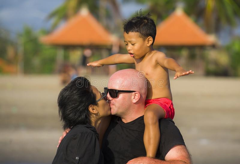 Happy and romantic mixed ethnicity couple Caucasian man and Asian Indonesian woman kissing and playing at tropical beach with stock images