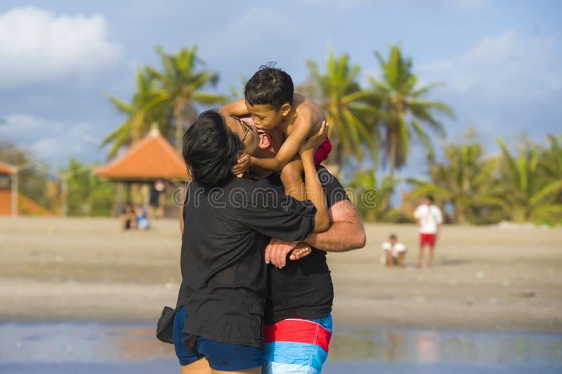 Happy and romantic mixed ethnicity couple Caucasian man and Asian Indonesian woman kissing and playing at tropical beach with royalty free stock photos