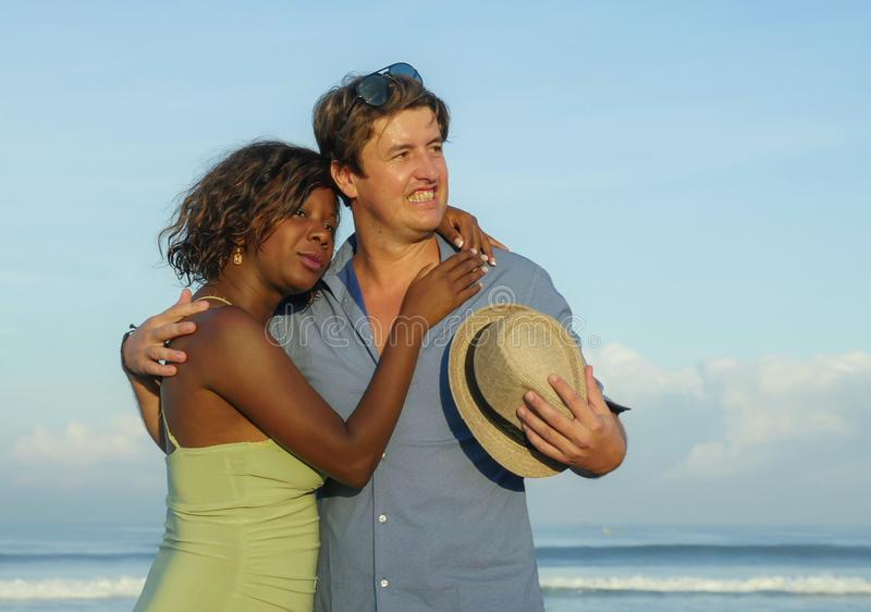 Happy and romantic mixed race couple with attractive black afro American woman and white man playing on beach having fun enjoying royalty free stock image