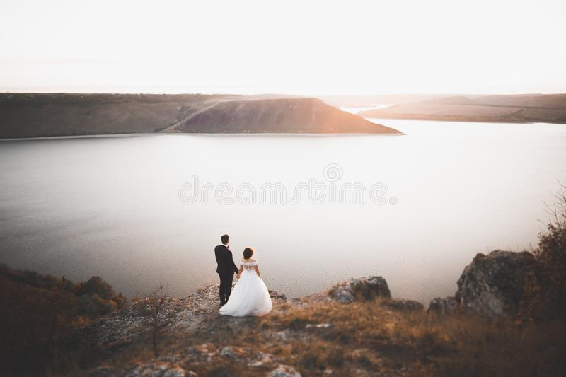 Happy and romantic scene of just married young wedding couple posing on beautiful beach stock photography