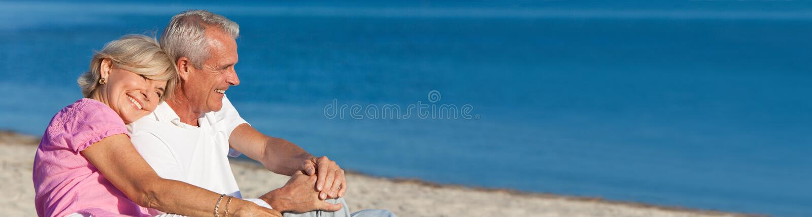 Happy Romantic Senior Couple Sitting Together on Beach. Panorama web banner happy romantic senior men and women couple together on a deserted beach royalty free stock images