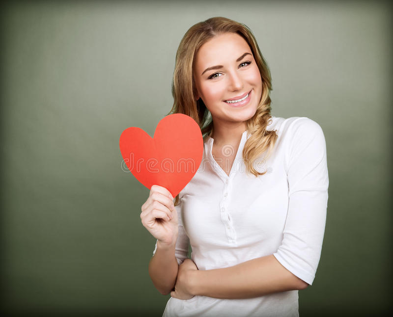 Happy romantic woman. Portrait of happy romantic girl with red paper heart-shaped postcard, romantic wishes, Valentine day celebration, love concept stock photos