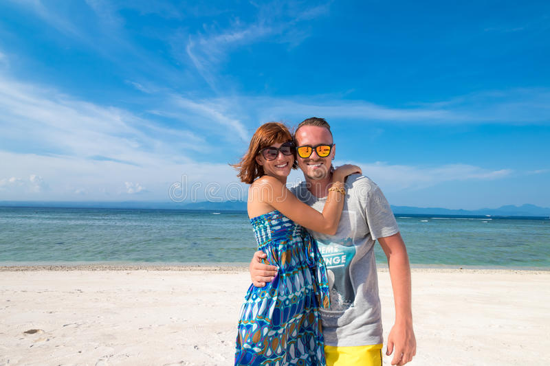 Happy romantic young couple on a beautiful beach with white sand. Caucasian couple having vacation on the tropical stock photo