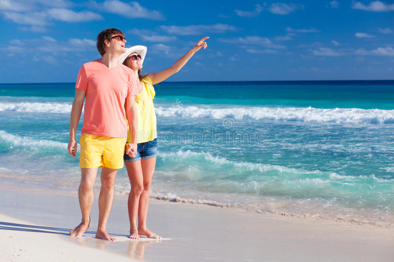 Happy romantic young couple pointing at the sky. Remote tropical beaches and countries. travel concept royalty free stock photos