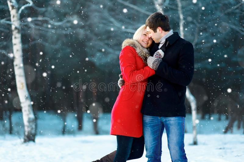 Happy romantic young couple walking in winter park on flying snowflakes snowy royalty free stock photos