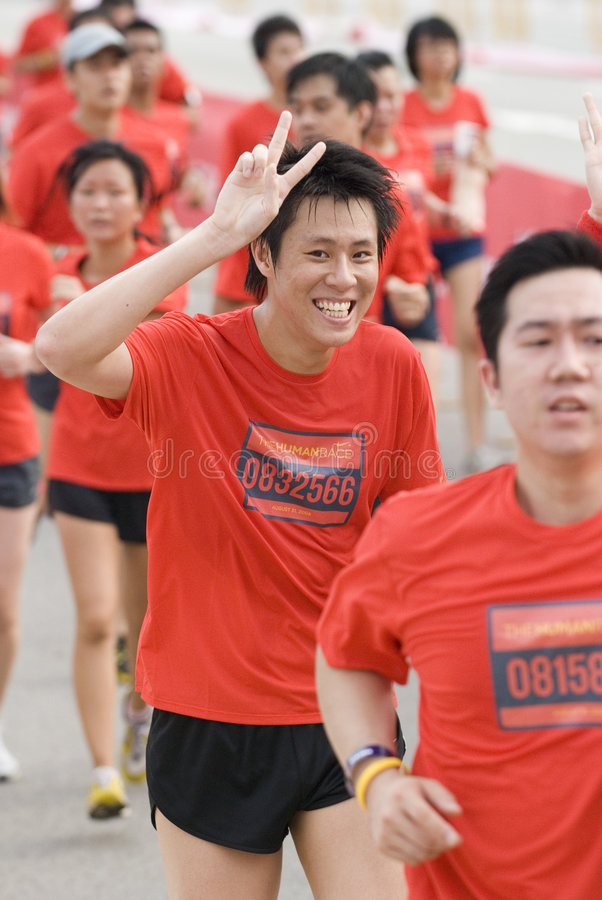 Happy runner showing the peace sign. Happy runner at the nike human race. this is a worldwide event held to start off at the same time singapore is the only stock image