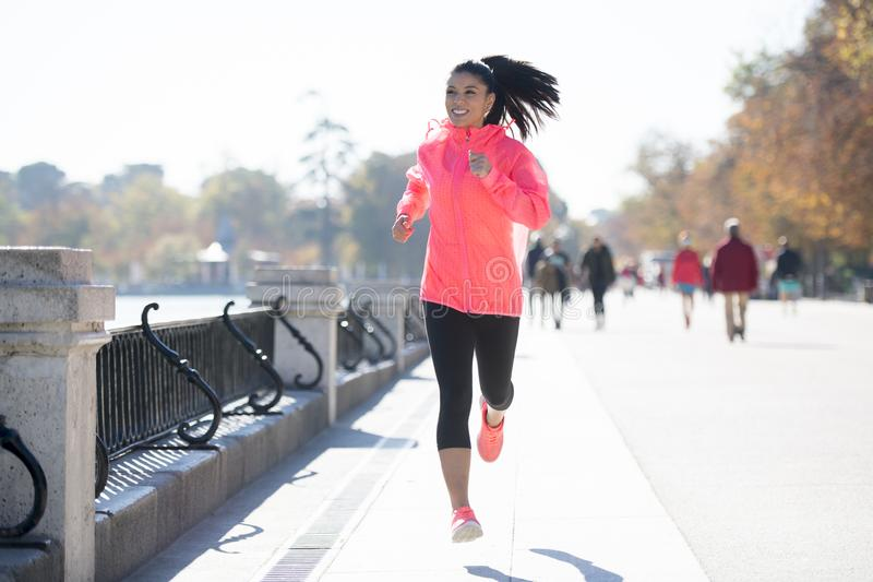 Happy runner woman in Autumn or Winter sportswear running and tr. Young attractive and happy runner woman in Autumn or Winter sportswear running and training on stock photos