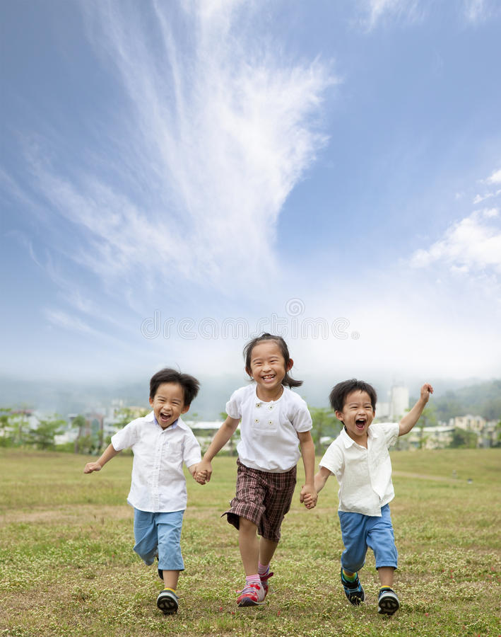 Happy running asian kids. And cloud background royalty free stock images