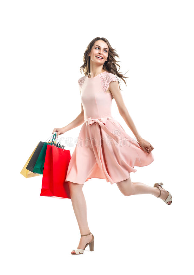 Happy running beautiful woman with many shopping bags. Happy running beautiful woman with many colorful shopping bags isolated on white background. Full length stock photo