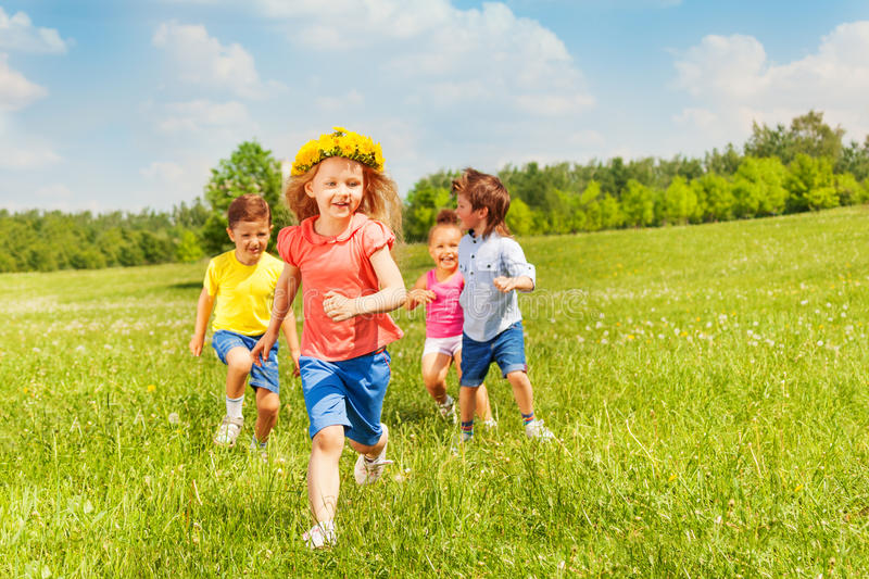 Happy running kids in green field during summer royalty free stock photography