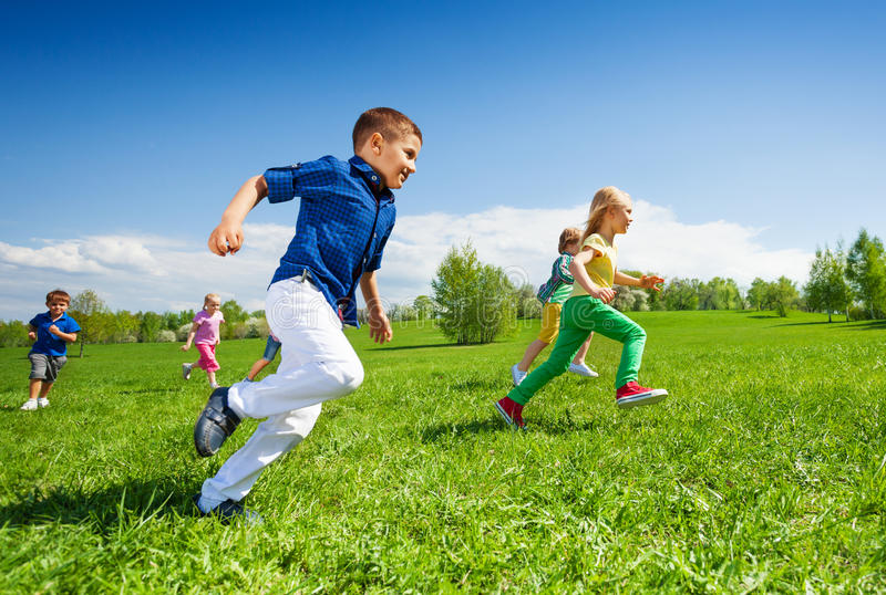 Happy running kids in the green park during day stock image