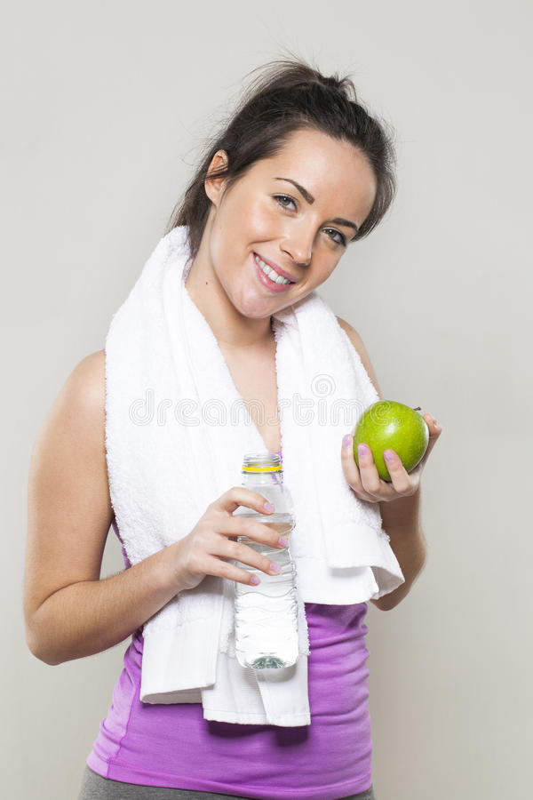 Happy 20s athletic girl with symbols of health and nutrition for sporty lifestyle in hands royalty free stock image