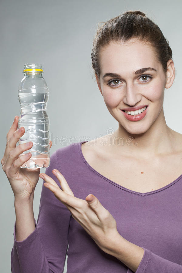 Happy 20s girl showing bottle of fresh zesty water. Smiling young beautiful woman wearing purple shirt displaying bottle of citrus mineral water royalty free stock photography
