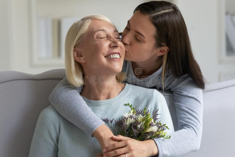Grownup daughter kisses mother gave her flowers congratulating at holiday. Happy 60s mother holding pretty spring flowers receiving congratulations at birthday stock photography