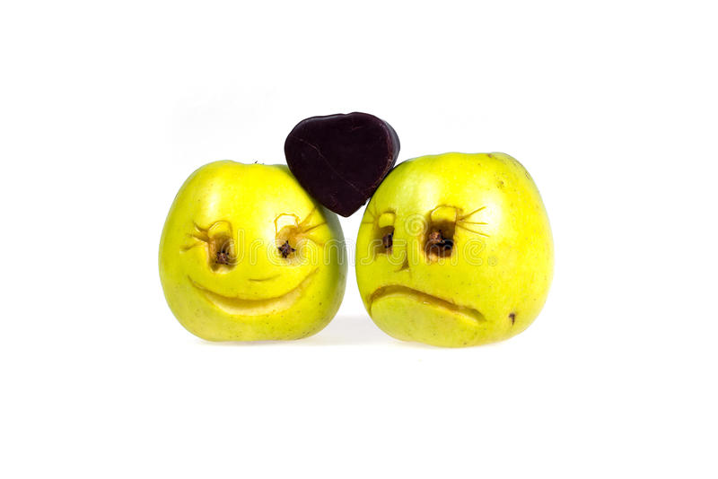 Happy and sad emoticons apples keep candy in the shape of a heart. Feelings, attitudes and emotions. Happy and sad emoticons apples keep candy in the shape of a royalty free stock photography