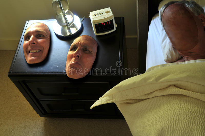 Happy or sad face to put on for the day. Two faces sit on a nightstand waiting for the faceless person to wake up royalty free stock photo