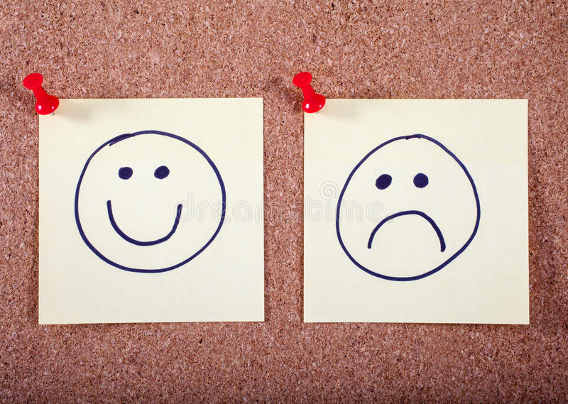 Happy and Sad Faces Pinned to a Noticeboard. A Happy and Sad face pinned to a noticeboard stock image