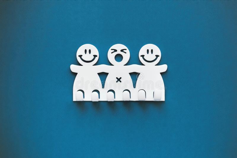 Happy and sad smiles. White Plastic figures on blue background stock photo