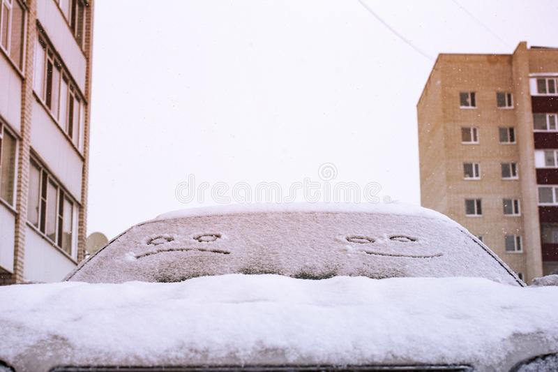 Happy and sad smiley emoticon face in snow on car windows, winter season joy and happiness concept stock photography