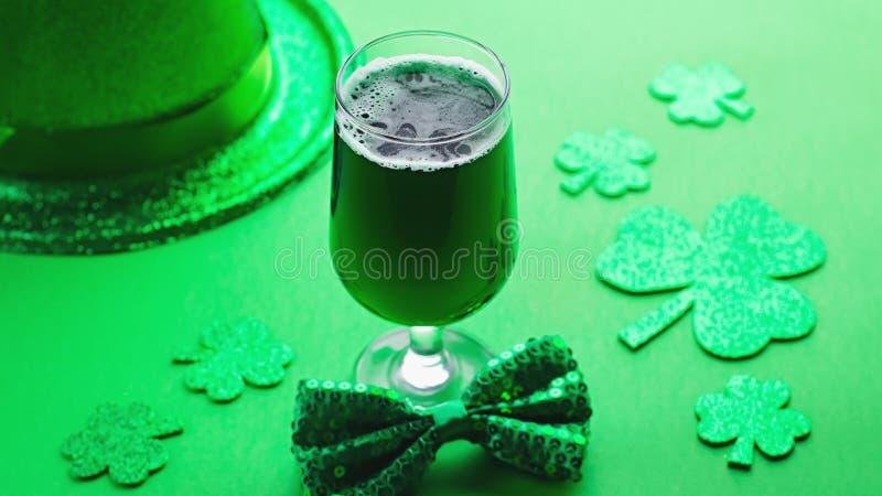Happy Saint Patrick`s Day greeting card with traditional symbols, shamrock, green attire. Green hat, bow tie, St Patricks Day. Shamrocks, golden confetti on stock photo