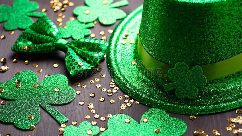 Happy Saint Patrick`s Day greeting card with traditional symbols, shamrock, green attire. Green hat, bow tie, St Patricks Day. Shamrocks, golden confetti on stock photos