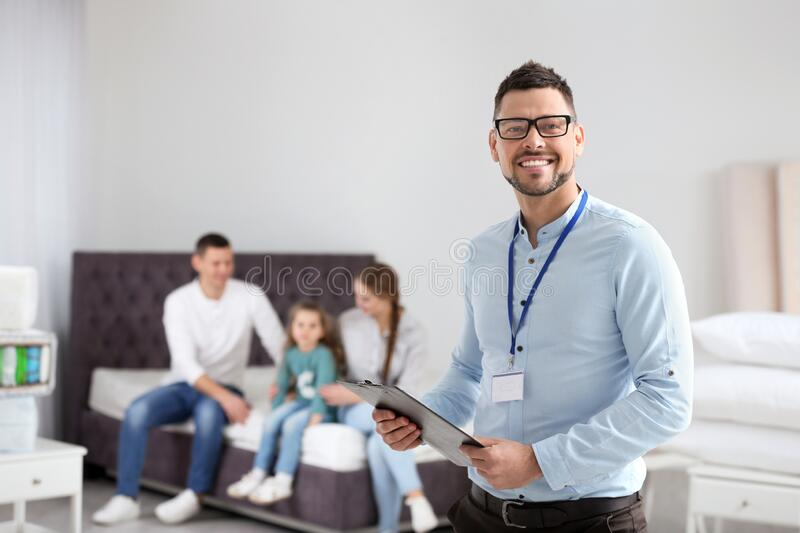Happy salesman and his clients in store stock photos
