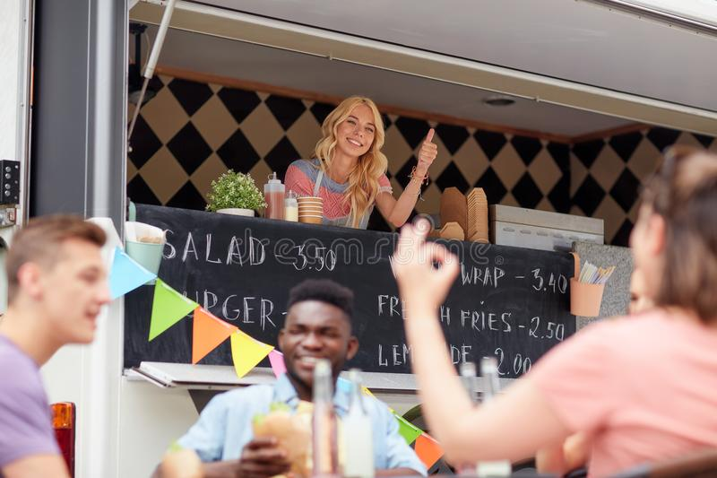 Happy saleswoman showing thumbs up at food truck. Street sale, customer service and people concept - happy saleswoman at food truck showing thumbs up royalty free stock image