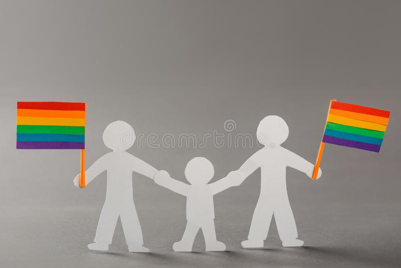 Happy same-sex family. With LGBT flags on gray. Paper people chain, gay marriage and child adoption legalization concept stock photography