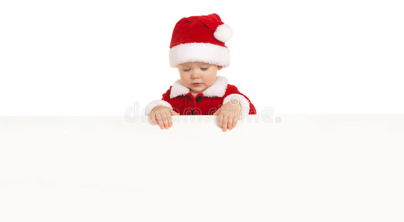 Happy santa baby with white blank board isolated on white. Small model in santa hat at studio holding paper poster. Christmas stock photo