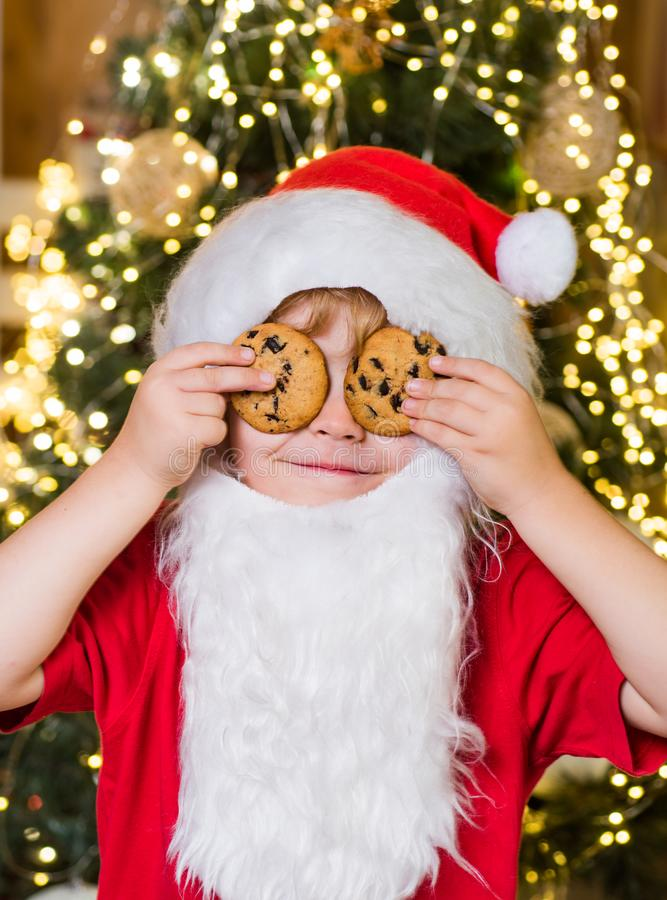 Happy Santa Claus - cute boy child eating a cookie and drinking glass of milk at home Christmas interior. Little Santa. Picking cookie and glass of milk at home stock images