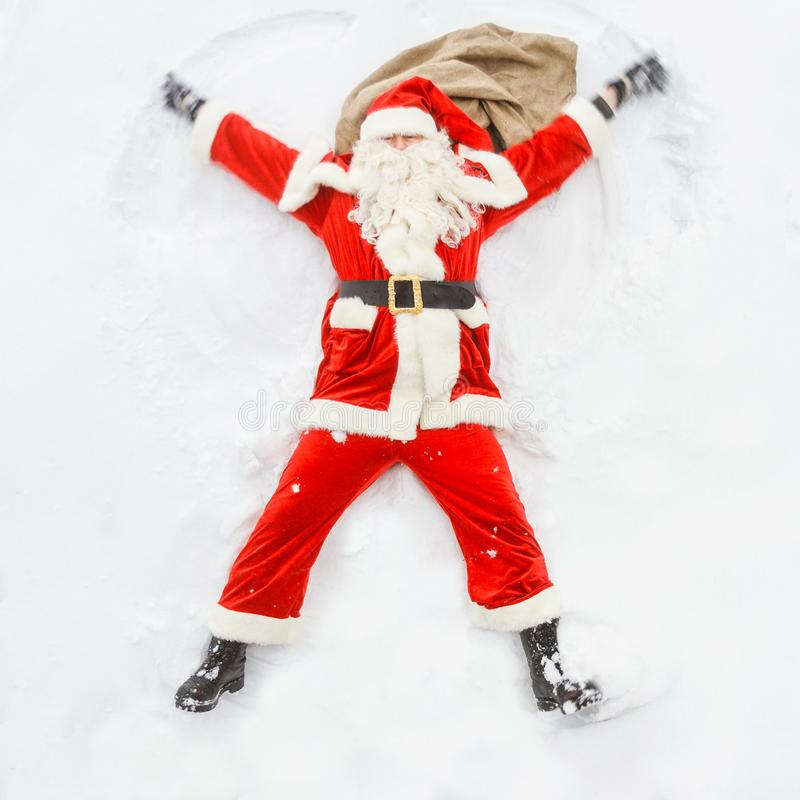 Happy Santa Claus makes a snow angel royalty free stock image