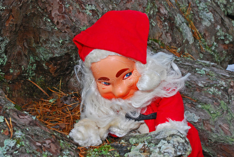 Happy Santa In The Woods. Closeup of a happy Santa Claus figure, sitting at the base of a tree royalty free stock photography