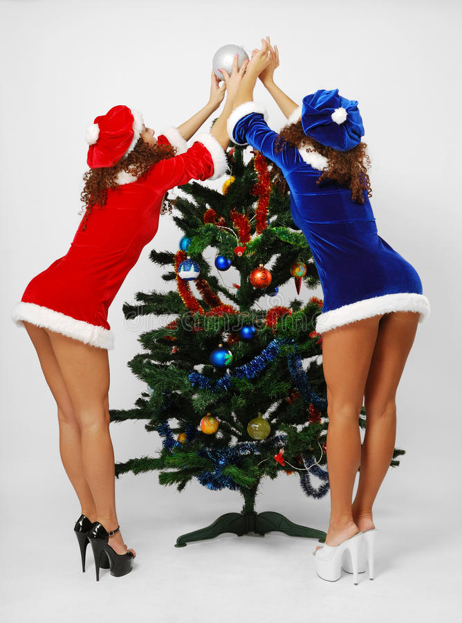 Happy Santas decorating the Christmas tree.