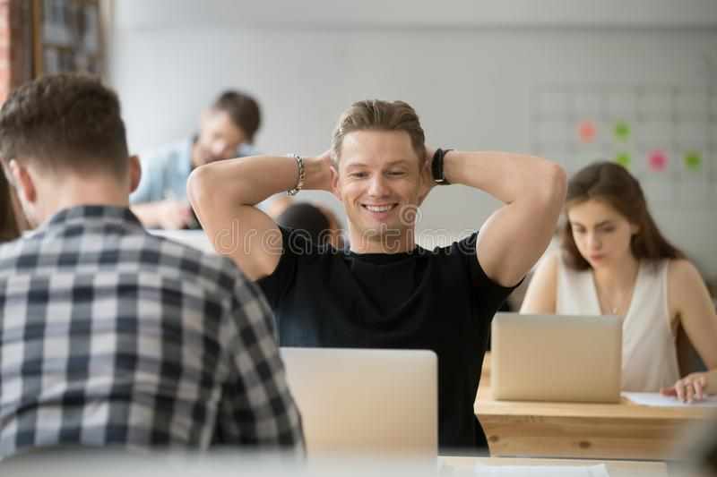 Happy satisfied businessman holding hands behind head looking at. Smiling businessman feels satisfied looking at laptop screen in coworking space, office stock photography