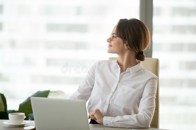 Happy satisfied businesswoman enjoying business success thinking stock image