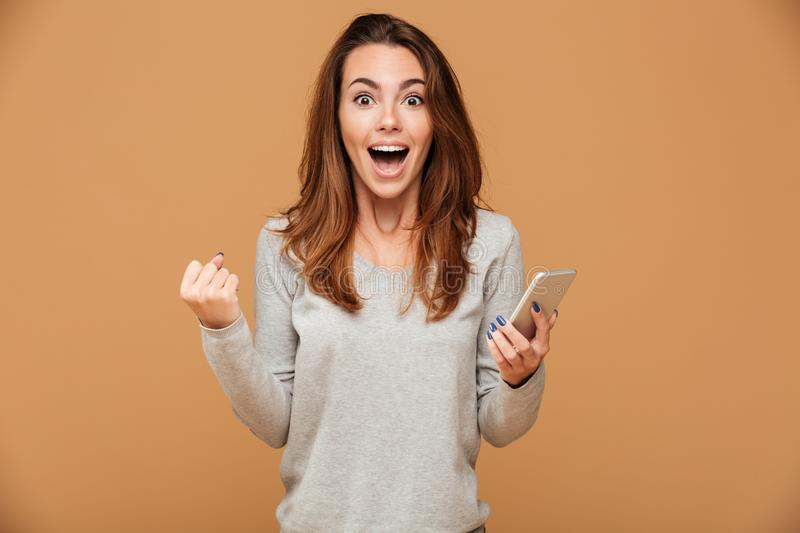 Happy satisfied girl in casual wear holding mobile phone, looking at camera. Over beige background royalty free stock images