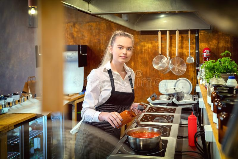 Happy satisfied woman adding condiments for taste in boiling pot with pasta sauce. Small business woman looking at camera and cooking in restaurant kitchen stock photo