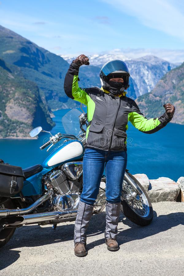 Happy and satisfied woman biker enjoys when standing in mountain stop in fjords of Norway royalty free stock image