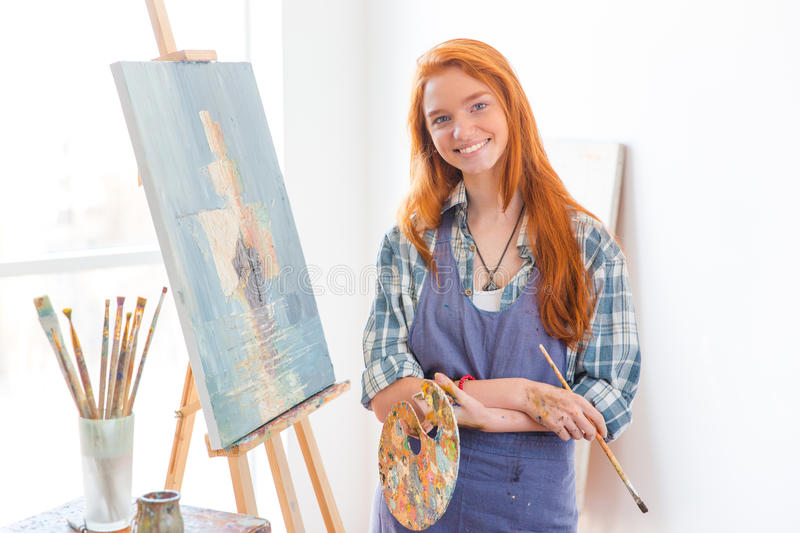Happy satisfied woman painter finished painting picture in art studio. Happy satisfied beautiful young woman painter in apron finished painting picture in art royalty free stock images