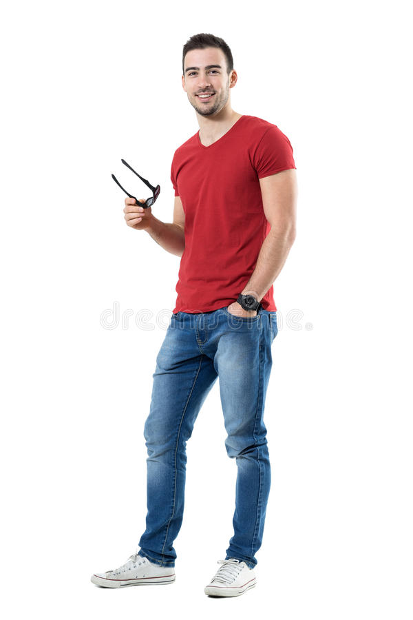 Happy satisfied young casual man holding sunglasses smiling at camera. Full body length portrait isolated over white studio background stock photo