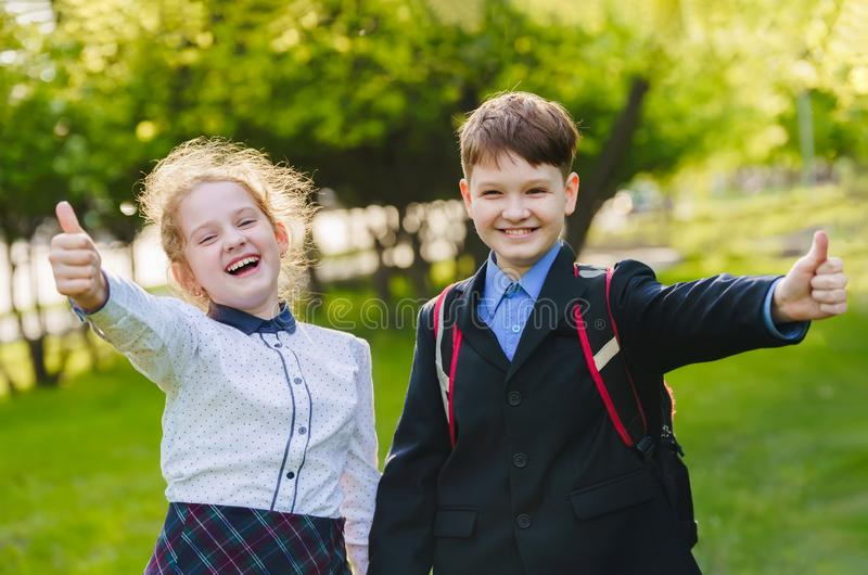 Happy school children giving a thumbs up gesture of approval and success stock photo