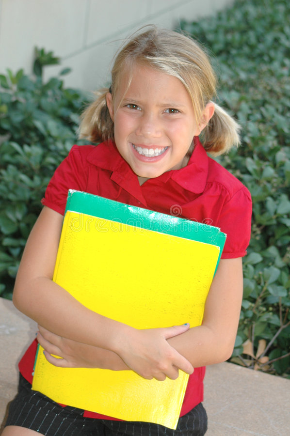 Happy School Girl. Happy smiling girl sitting in front of her school with folders in her arms stock images