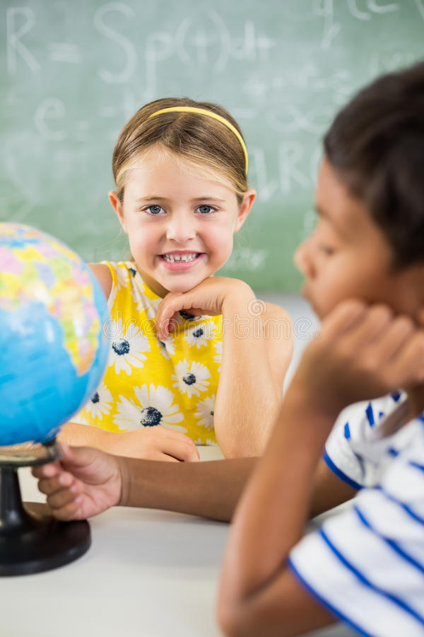 Happy school kids with globe in classroom stock images