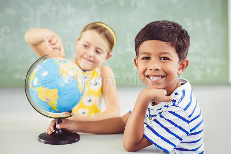 Happy school kids with globe in classroom stock photos
